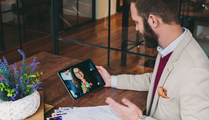 Man in an office having video interview with woman on tablet