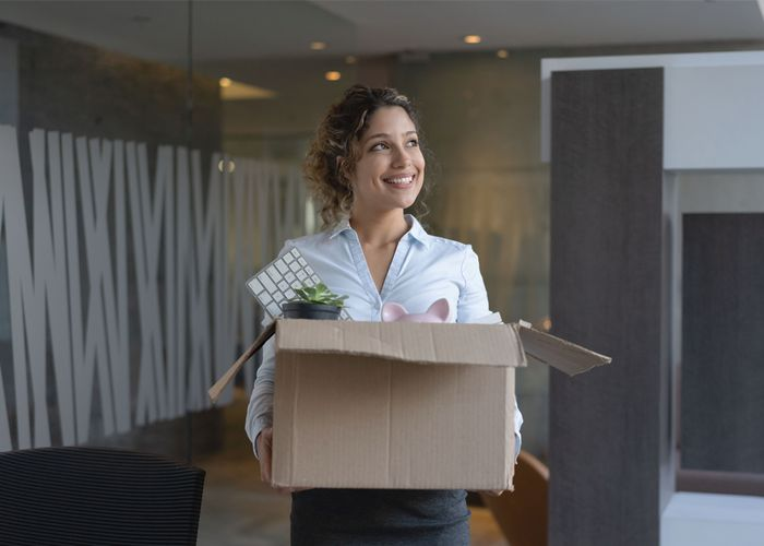 Women smiling as she leaves office with box of her belongings